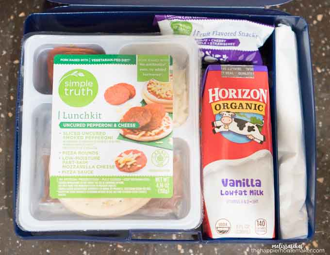 An above picture of a lunchbox with milk, a lunch kit and snacks