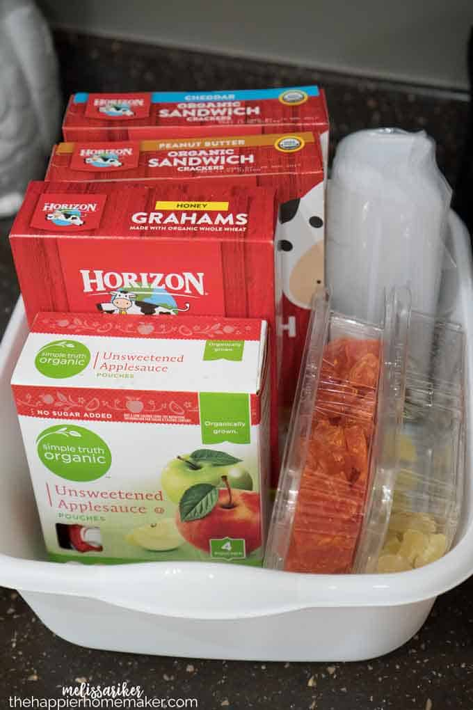 A plastic organization bin with dried fruit, applesauce and graham crackers packed inside