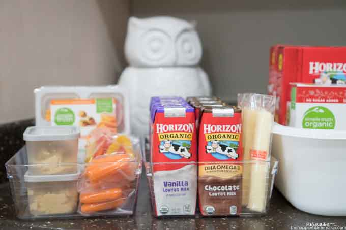 Two organizing bins with snacks including cheese sticks, milk cartons and carrots with a white ceramic owl in the background