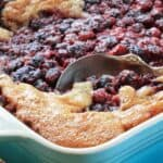 mixed berry cobbler in a blue baking dish with silver spoon
