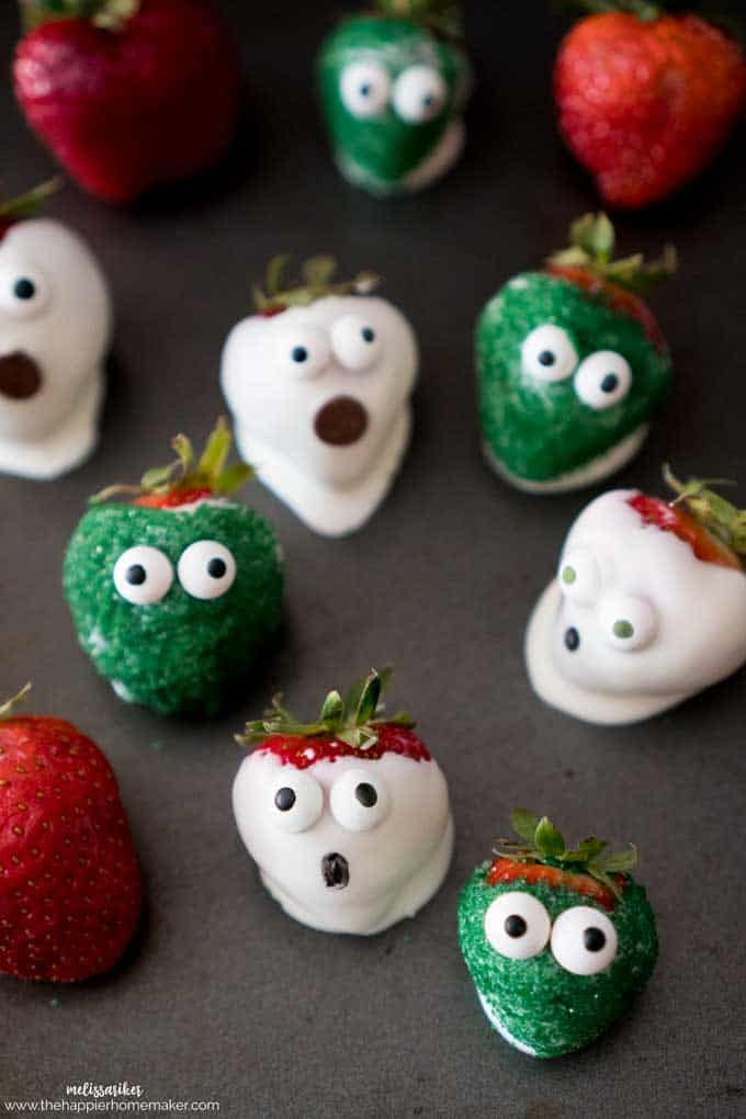 Several white and green chocolate covered strawberries made to look like monsters for Halloween