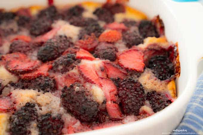 close up of strawberry and blackberry cobbler in white casserole dish