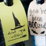 A close up of wine bottles with tags reading drink up witches and you've been boozed
