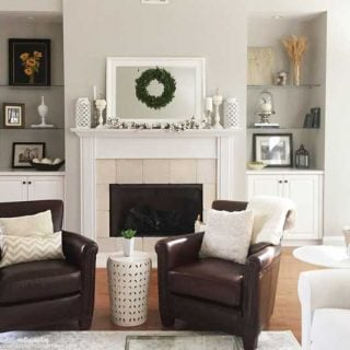 Two leather chairs sitting in front of a fireplace with a white mantel