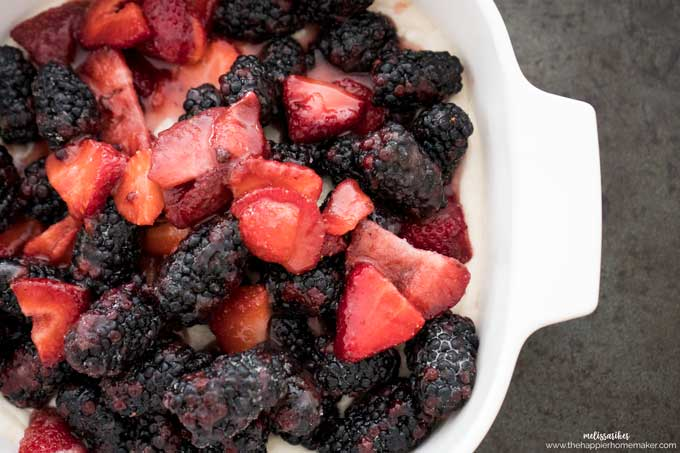 strawberry and blackberry cobbler before cooking in a white casserole dish