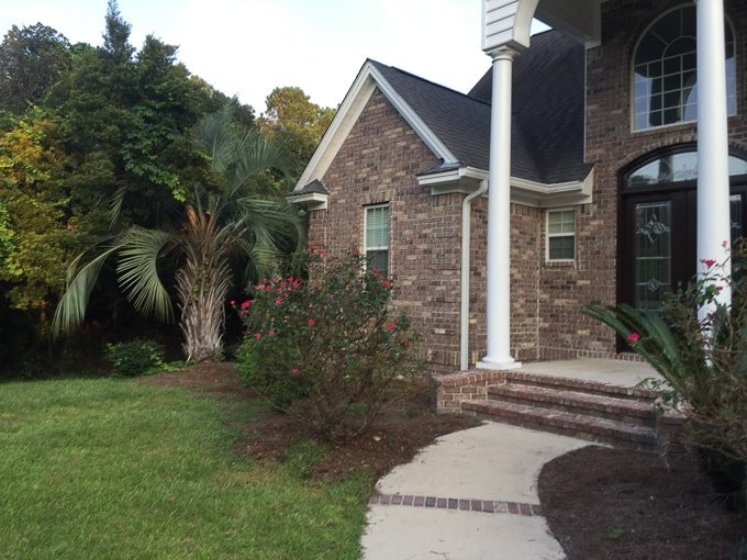 entry to large brick home with roses and palm tree