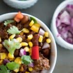 A bowl of chili garnished with fresh corn, cilantro, onion and red pepper in a white bowl