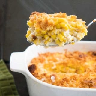 A close up or a spoon full of traditional corn pudding in a white baking dish