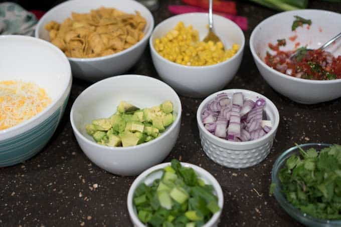 The ingredients consisting of corn, onion, green onion, avocado for chili in separate bowls