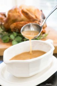 ladle with turkey gravy in white gravy boat with roast turkey in background