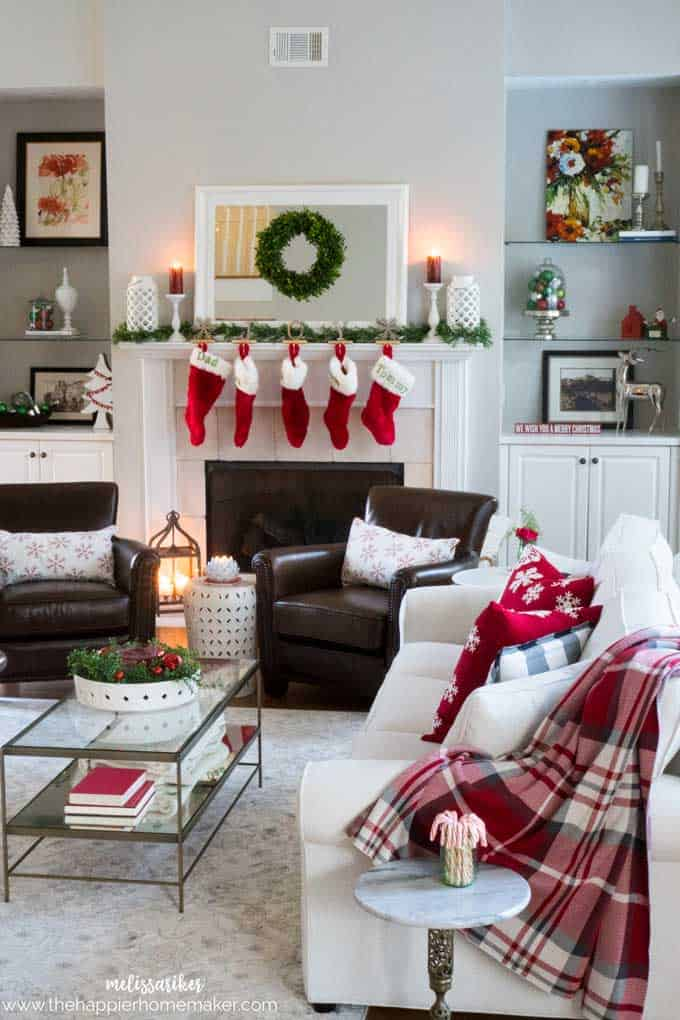 A living room decorated for Christmas with stockings hung on the mantle
