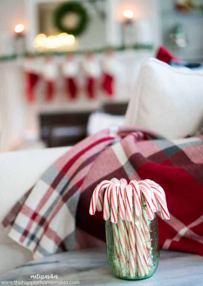 A close up of candy canes in front of a Christmas decorated living room