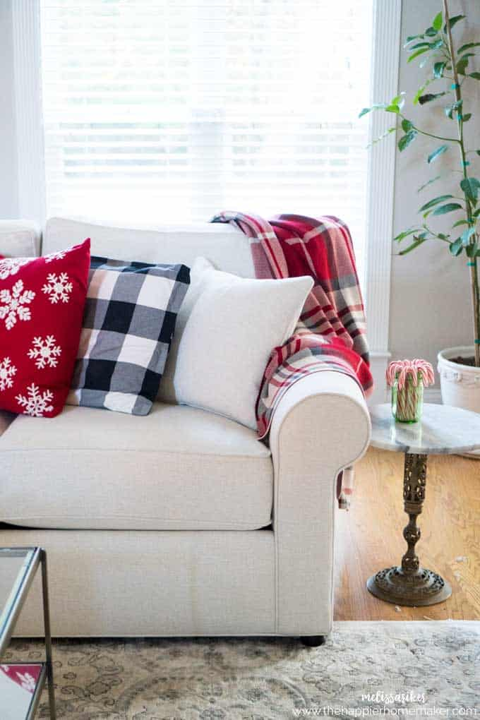 A white sofa with a buffalo check throw and assorted throw pillows