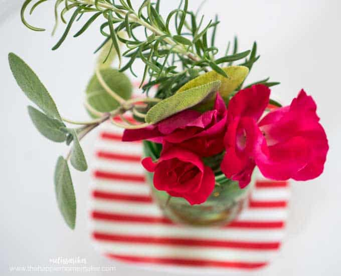 overhead view of red roses and rosemary in mason jar vase sitting on red and white striped plate