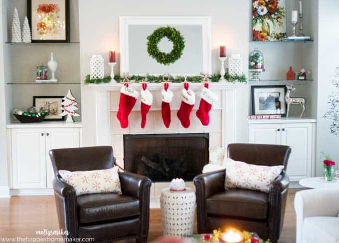 A living room decorated for Christmas with stockings hanging from the mantel, a mirror with wreath, and two leather chairs in the foreground