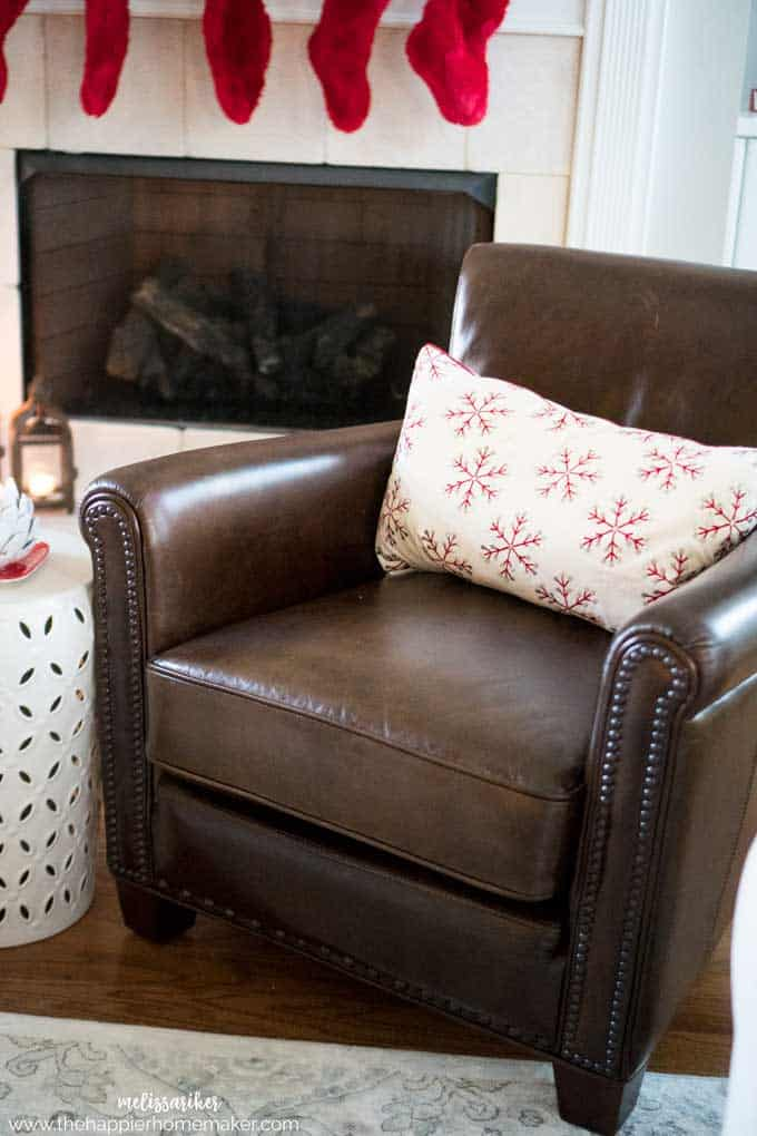 A brown leather chair with a decorative red snowflake pillow