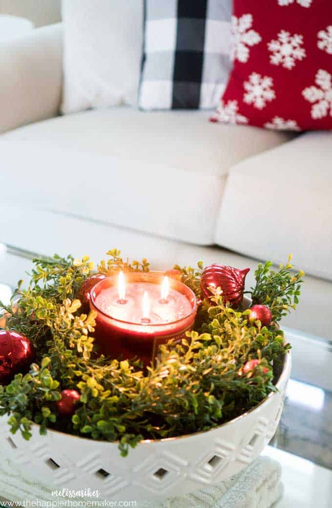 A close up of a red holiday candle surrounded by Christmas ornaments and faux box wood garland