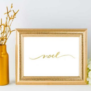 A gold picture frame with the word Noel written in calligraphy next to a gold vase of wheat