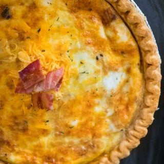 A close up a baked quiche garnished with bacon