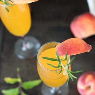 A Bellini and Champagne cocktail garnished with a peach and rosemary