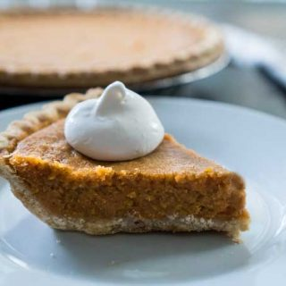 sweet potato pie on a white plate with whipped cream
