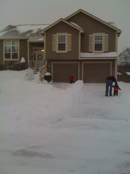 A house covered in snow with family out front