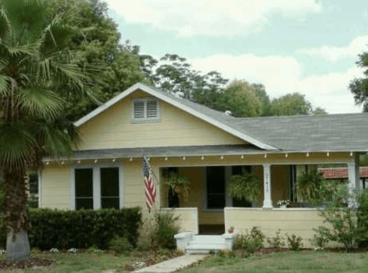 yellow bungalow with American flag and ferns hanging on porch