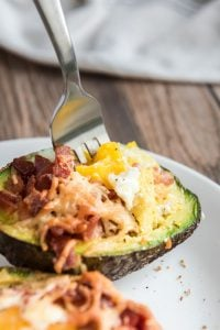 Baked Eggs and Avocado with Bacon and Cheese with a fork taking a bite