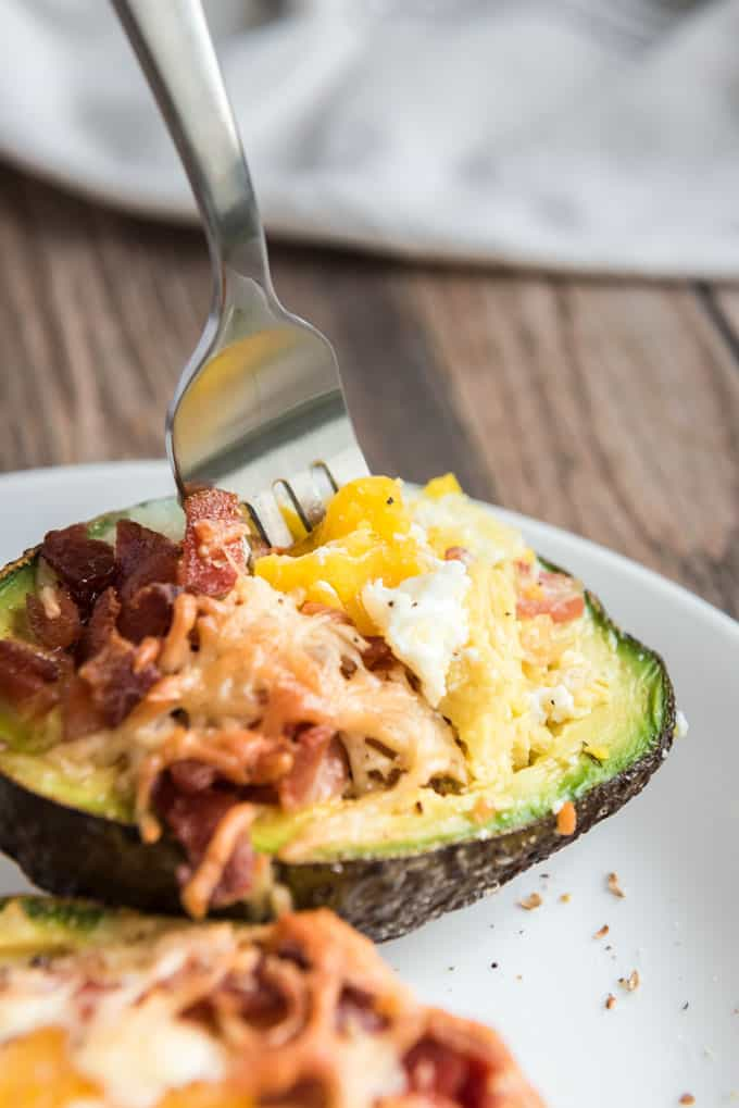Fork with bite of Baked Eggs and Avocado with Bacon and Cheese on a white plate