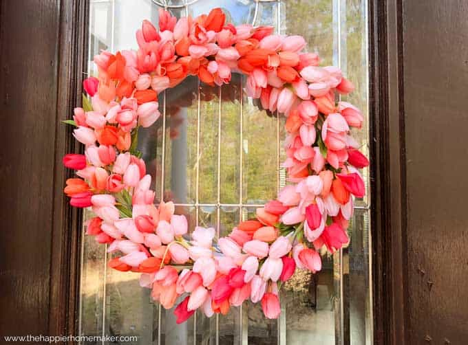 A close up of a pink tulip wreath hanging on a glass pane in a wooden door