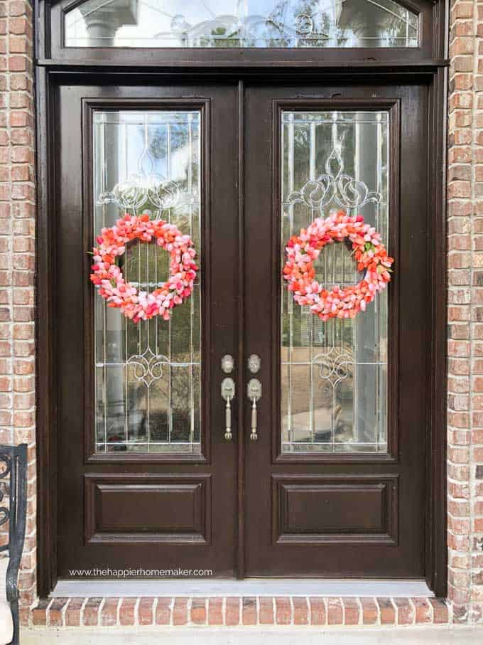 large double wood doors with each holding a pink wreath of tulips
