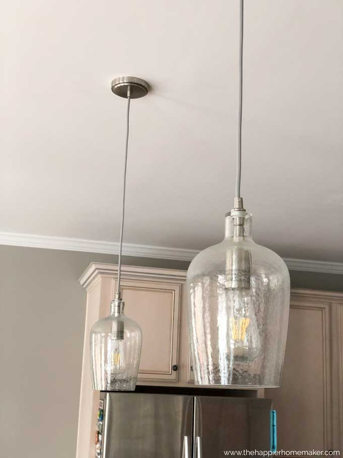 A close up of two hanging pendant lights with a nickel finish and edison bulbs
