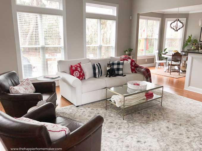 A living room with a fabric white sofa, glass coffee table, and two leather chairs