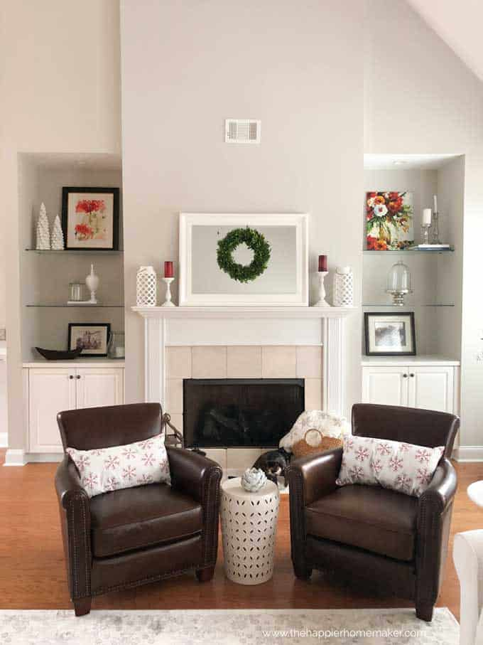 A living room with two leather chairs and a fireplace in the background
