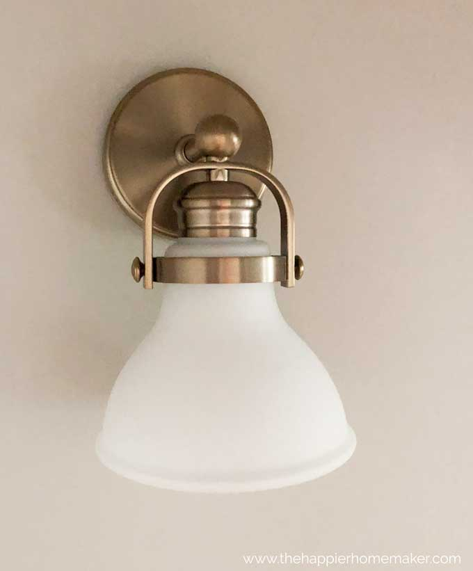 A close up of an antique brass wall lamp with frosted globe