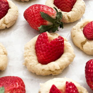 A close up of cookie with heart shaped strawberries on top