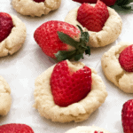 A close up of cookies with heart shaped strawberries on top