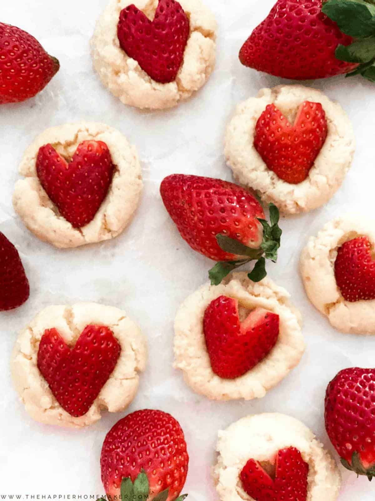 Strawberry Cheesecake Cookie Recipe - Easy, delicious light and fluffy cookies with a creamy center, topped with a heart shaped strawberry. Perfect Valentine's Day dessert recipe!