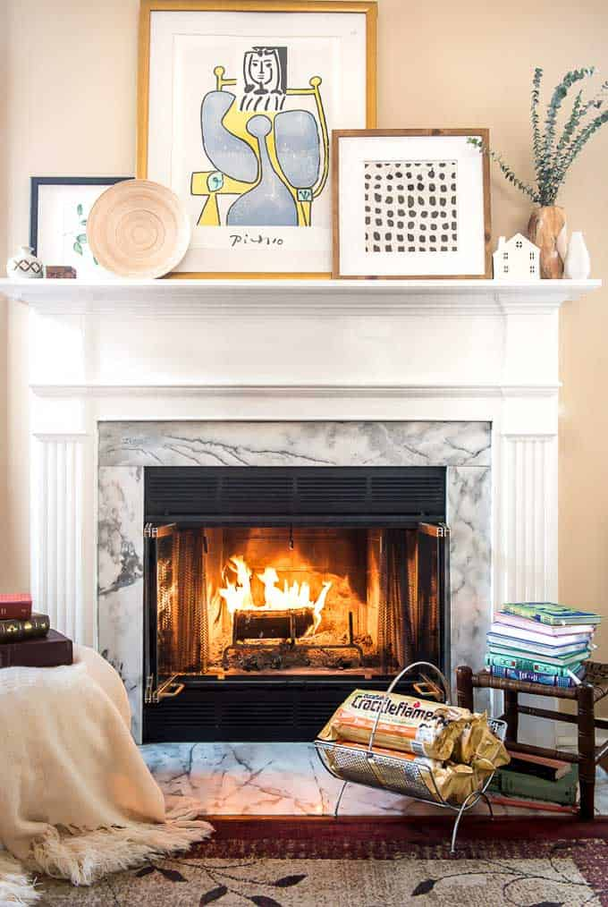 Decorated fireplace with pictures, books and chair