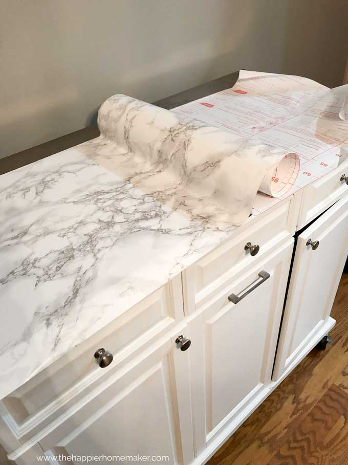 white rolling kitchen island with top being covered in marble contact paper