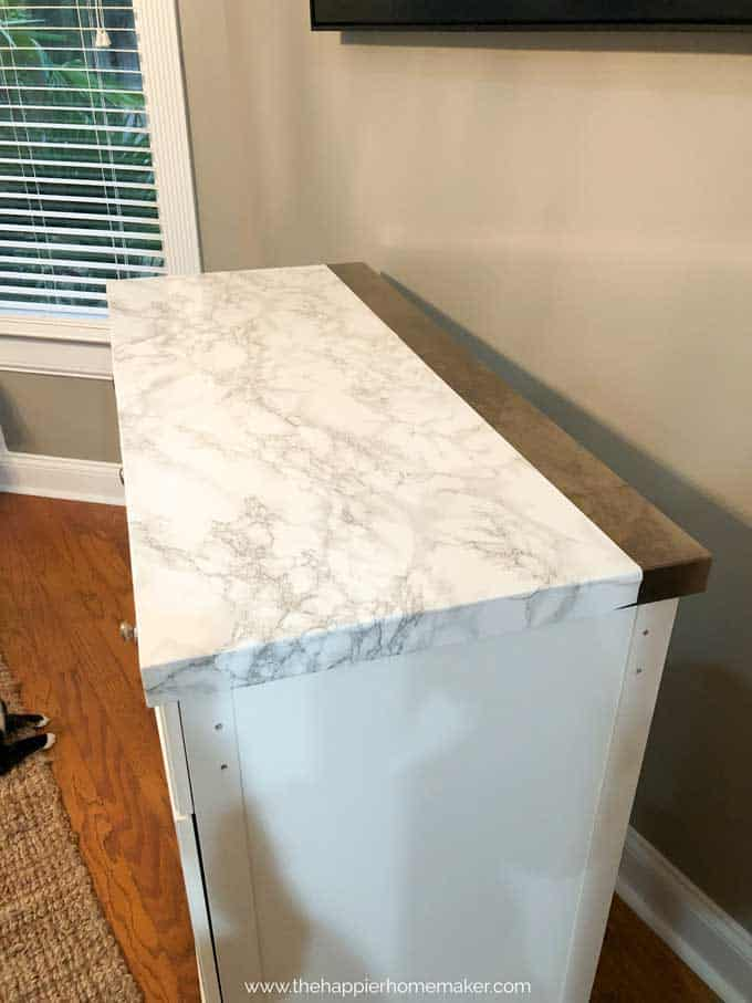 Marble contact paper covering most of the top of a white rolling kitchen island