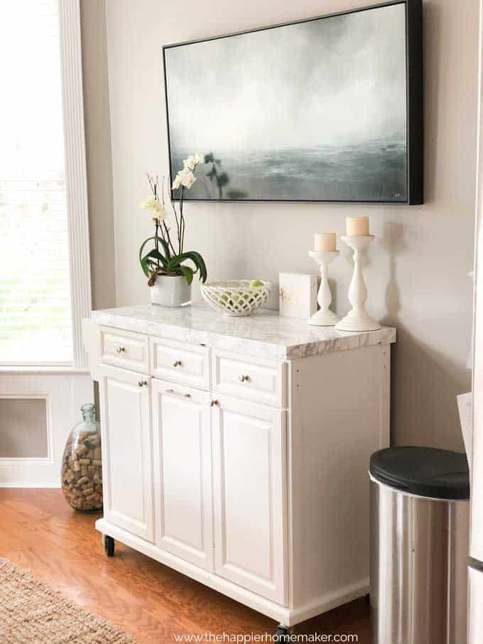 white rolling kitchen island with marble top below a large ocean painting