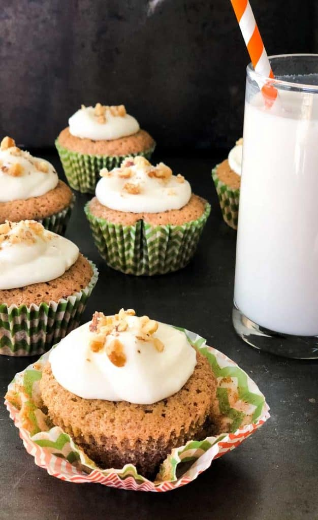 carrot cake muffins with whipped cream and crushed walnuts on top with glass of milk