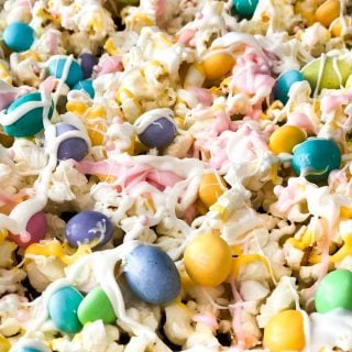 close up of popcorn with pastel M&Ms and drizzled white chocolate