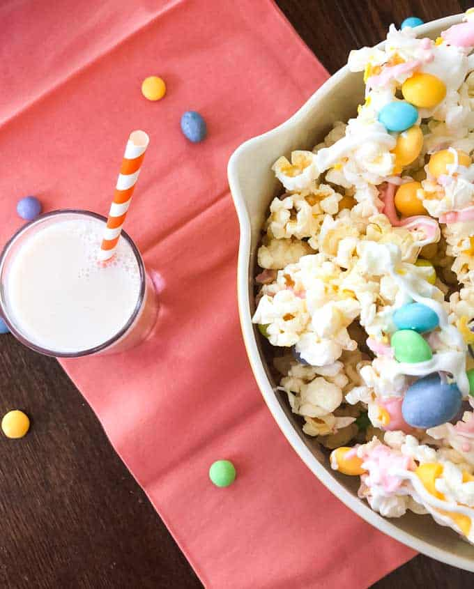 overhead view of bowl of popcorn with pastel candies in it and glass of milk