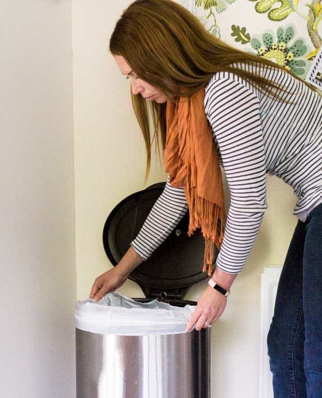 woman changing trash can bag with orange scarf and striped shirt
