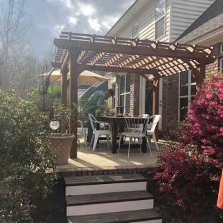raised patio with large wooden pergola and dining set