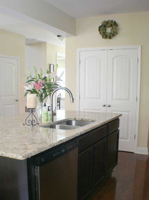 kitchen island with dark cabinets and granite countertop and vase of flowers