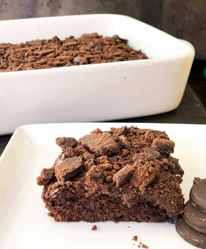A piece of chocolate thin mint brownies on white plate with casserole dish of brownies in the background