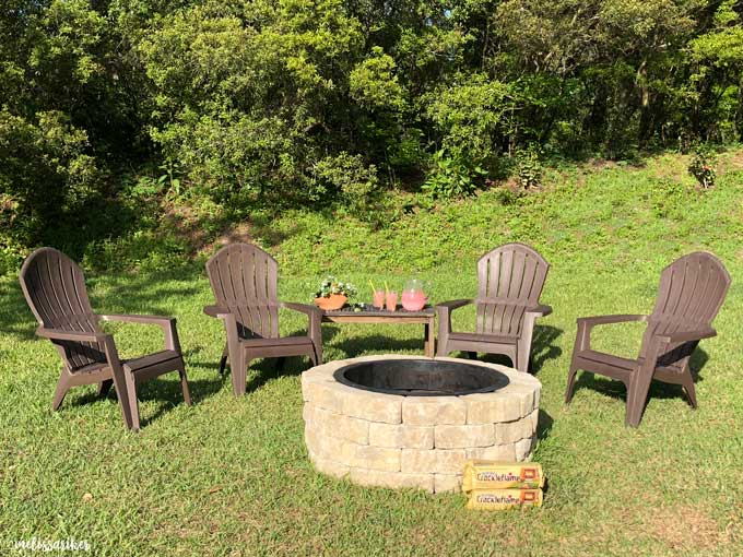 Adirondack chairs surrounding a stone fire pit in the grass